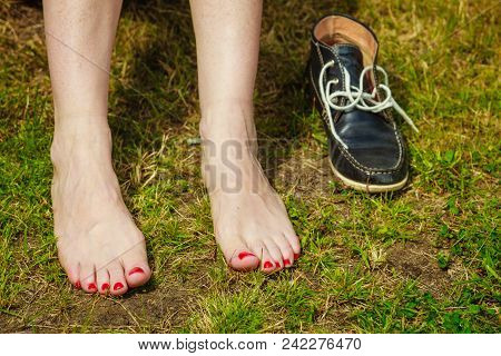 Female Feet On Green Grass Ground Next To Her Shoes. Woman Relaxing Outdoor During Warm Weather