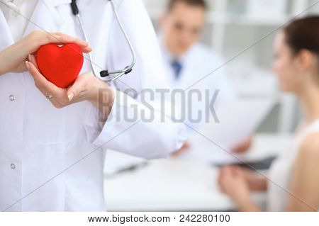 Female Doctor Holding Heart In Her Hands.  Doctor And Patient Sitting In The Background. Cardiology