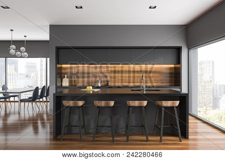 Gray And Wooden Wall Kitchen Interior With Gray Countertops, A Bar With Stools And A Dining Room Tab