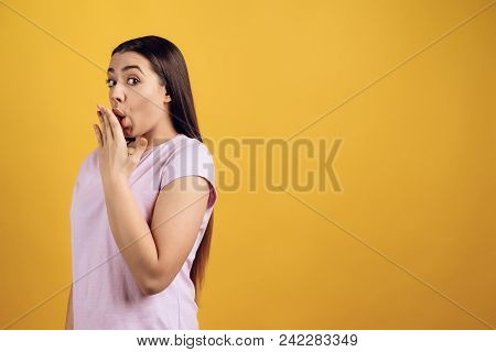 Young Shy Girl Covers Mouth With Palm. Isolated On Yellow Background. Studio Portrait.