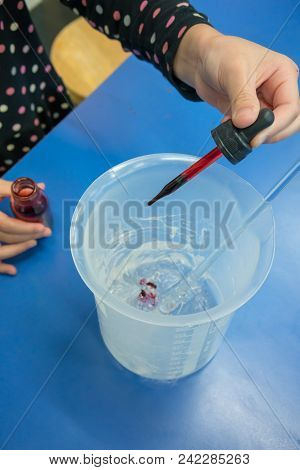 Girl Using Droplet To Add Red Color Into A Plastic Beaker On Blue Table. Diy Hand Gel Experiments Fo
