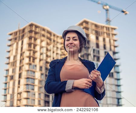 Beatiful Business Woman Engineer Is Standing With Plan Papers. Construction Project With Crane Is On