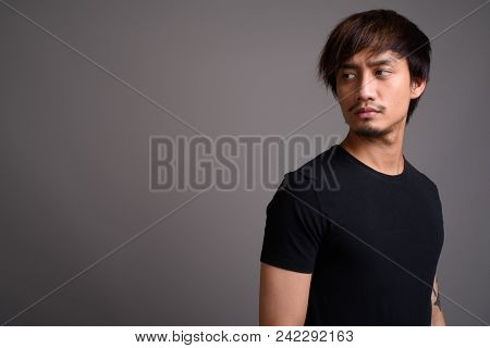 Studio Shot Of Young Asian Man Against Gray Background