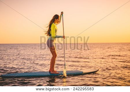 Sporty Young Woman At Stand Up Paddle Board With Beautiful Sunset Colors