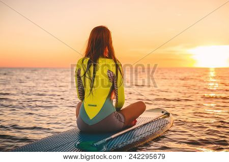 Woman Relaxing On Stand Up Paddle Board, Quiet Sea With Warm Sunset Colors.