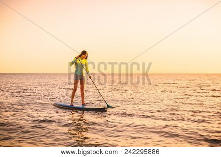 Sporty Young Woman Stand Up Paddle Surfing With Beautiful Sunset Or Sunrise Colors