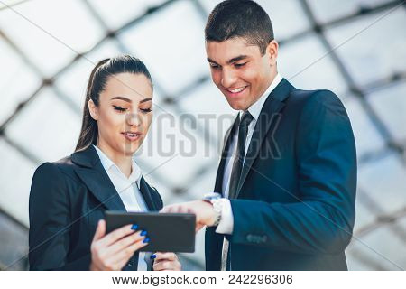 Businesspeople Discussing While Using Digital Tablet Outdoor