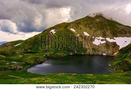 Glacier Lake Capra At The Foot Of The Mountain. Lovely Summer Scenery On A Cloudy Day. Popular Trave