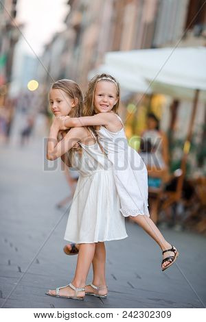 Adorable Little Girls In Pietrasanta In Toscany. Portrait Of Kids Walking At Small Italian Town On I