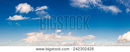 Panorama Of Beautiful Cloudscape On A Blue Sky. Wonderful Summer Weather Background