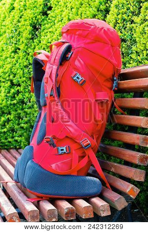 Red Travel Backpack Close Up On The Bench In The Garden. Travel Concept. Backpacker Style