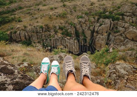 Photo Of Female And Male Legs In Gumshoes On The Background Of The Canyon
