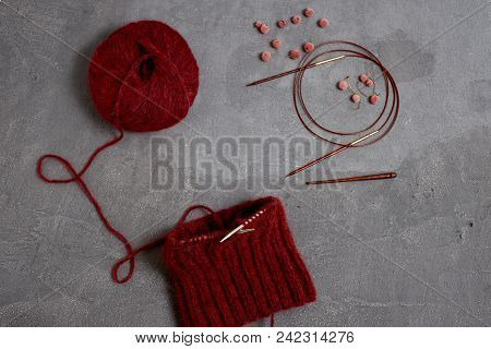 Red Unfinished Sweater With A Ball Of Threads On A Gray Background Closeup.