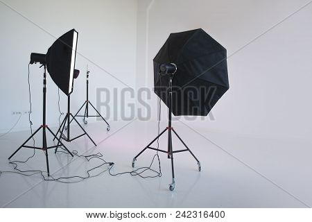 An Empty Photo Studio With  White Cyclorama. Monoblocks With Flashes Using Softboxes Of Different Sh