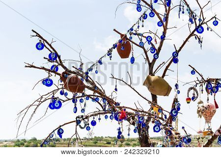 Travel To Turkey - Tree Decorated By Local Amulets In Goreme National Park In Cappadocia In Spring
