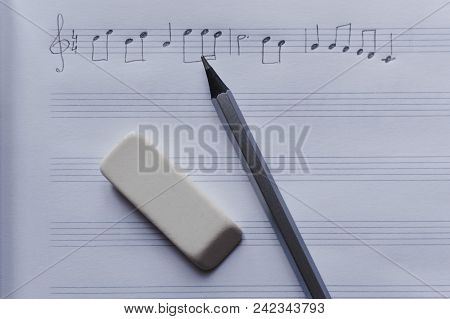 Close-up View Of The Eraser And Pencil Laying On The Blank Music Sheets With Handwritten Music Notes