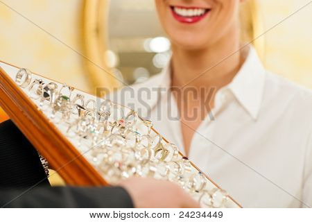 Shop assistant at the jeweler with jewelry