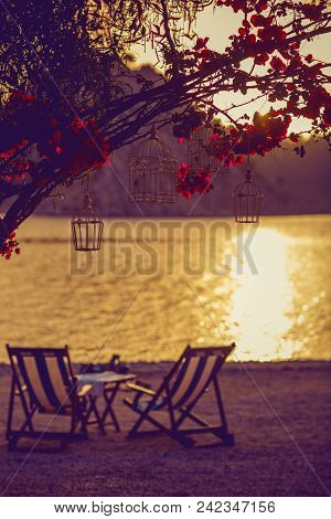 Loungers At The Seaside At Sunset. Flowering Begonvil Branch On The Beach At Sunset