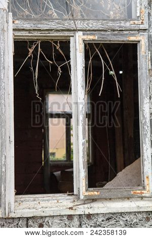 Broken Window Of An Abandoned House, With Naked Walls (no Plasterwork)
