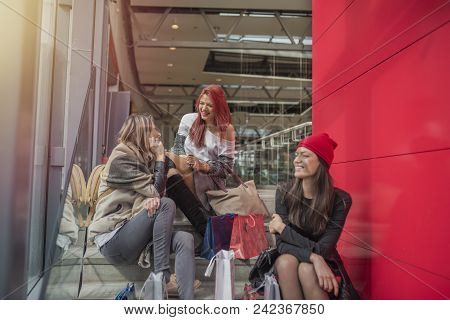 Three Pretty Young Girls Taking In Shopping Mall, After Done Shopping. Attractive Women With Shoppin