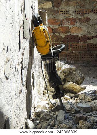 Demolition Of Walls. Demolition Hammer Against The Destroyed Wall