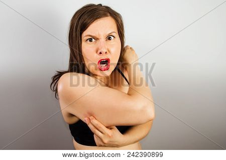 Young Fat Woman Holds On The Fat Fold On The Arm On Light Gray Background