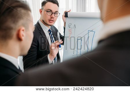 Business Briefing And Goals Visualization. Company Managers Writing On The Flip Chart In Office Boar