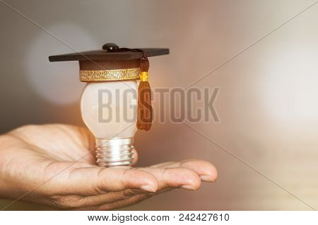 Education Or Graduate Study Creative Concept: Mini Graduated Hat With Light Bulb  On Hands In Blur B