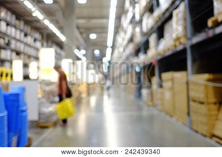 Blurred A Large Warehouse Area With Full Of Stock Products On The High Shelfs And Customers Watching