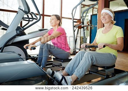 Two happy senior women training on rowing machines in contemporary leisure center
