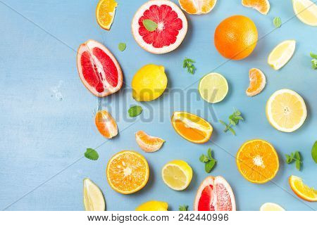Citrus Slices Food Pattern On Blue Background With Copy Space - Assorted Citrus Fruits With Mint Lea