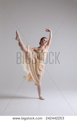 Making A Dance! Graceful Attractive Charming Young Ballerina In Beige Outfit Posing On Toes On The S