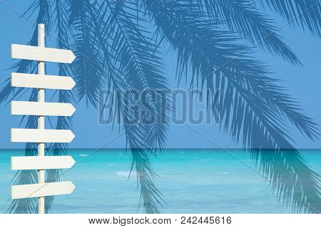 White Wooden Arrow Signpost Over Blue Ocean Palm Landscape Turquoise Water And Horizon