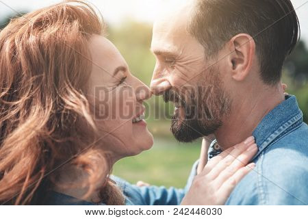 Close Up Profile Of Cheerful Mature Loving Couple Touching Their Noses And Smiling. They Are Looking