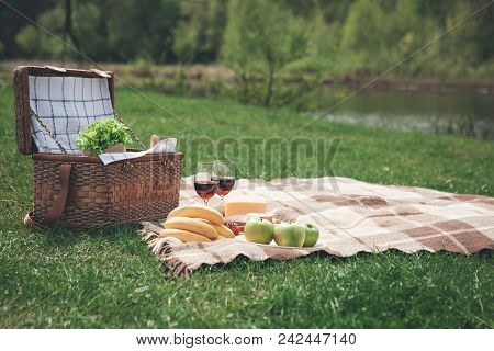 Everything For Romantic Picnic. Healthy Food And Glasses Of Wine On Blanket. Picnic Basket Is On The