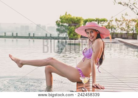 Swimsuit Concept. Beautiful Girl Wearing Pink Swimsuit. Beautiful Girl In Swimwear Is Relaxing At Th