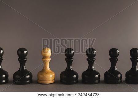 Line Of Black Pawns With One White Inside. Uniqueness Of Individuals In Mass, Loneliness Concept