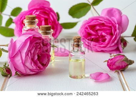 A Bottle Of Essential Oil With Roses On A White Wooden Table