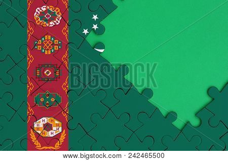 Turkmenistan Flag  Is Depicted On A Completed Jigsaw Puzzle With Free Green Copy Space On The Right
