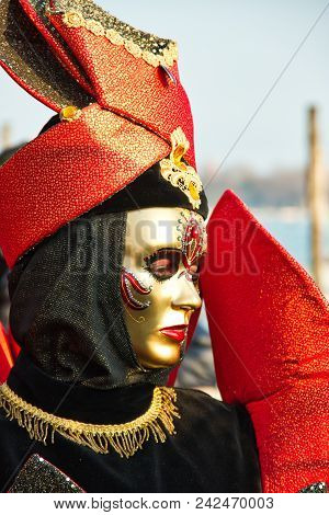 A Costumed Reveler Of The Carnival Of Venice In A Red And Black Costume Looking To The Right.