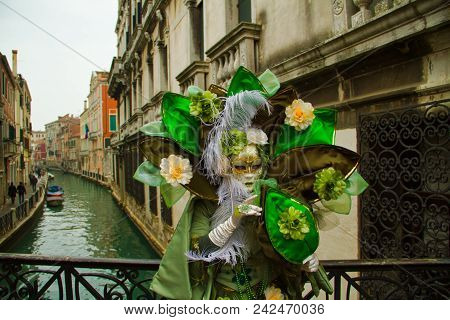 A Costumed Reveler Of The Carnival Of Venice In A Green Costume Looking At The Camera While On A Bri