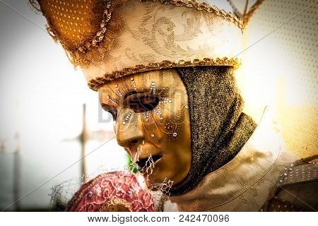 Costumed Reveler Of The Carnival Of Venice In A Gold Costume And A Black Vignette.