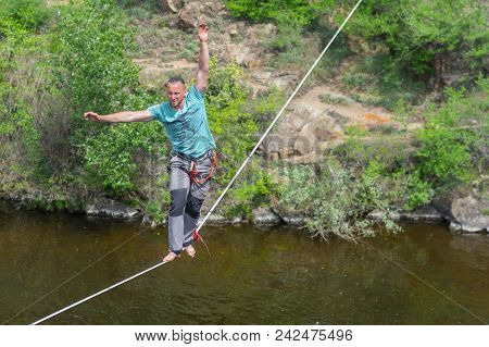 Dnipro, Ukraine - May 06, 2018:young Rope-walker Trying To Keep Balance While Walking On A Rope Over
