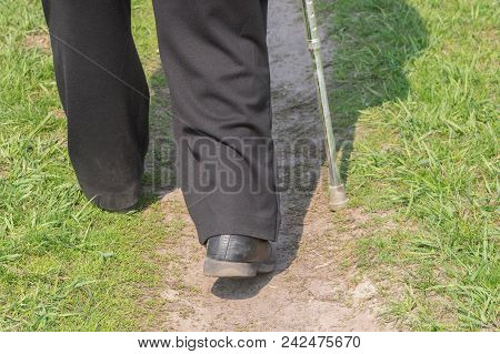 Man With Walking Stick Wearing Old Scratched Shoes Walking On An Earth Road (rear View)