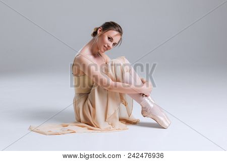 Tenderness Is Inside! Young Attractive Graceful Gentle Ballerina Sitting On The Floor And Posing At