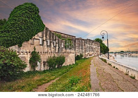 Arles, France: landscape from the riverbank of the Rhone river at sunset with the ancient houses and the bridge poster