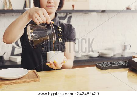 Unrecognizable Barista Pouring Coffee At Cafe Counter. Portrait Of Young Girl In Uniform At Her Work