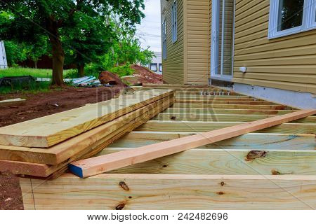 A Installation Wooden Deck Or Patio New Home, Timber Deck Being Constructed