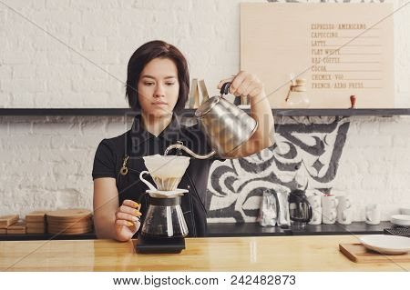 Barista Preparing Pourover Coffee At Cafe Counter. Portrait Of Young Girl In Uniform At Her Working