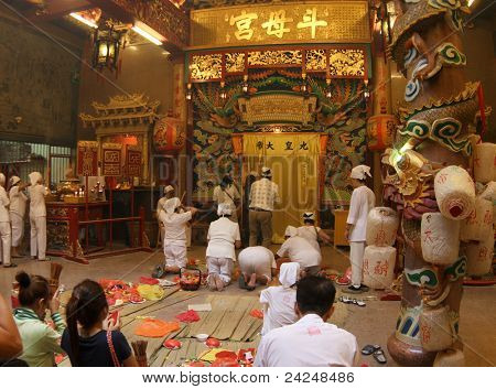 AMPANG, MALAYSIA – OCT 05: Taoist devotees chant, meditate and pray at the main hall of the Lam Thian Kiong Temple at the annual 'Nine Emperor Gods' Festival on October 05, 2011 in Ampang, Malaysia.